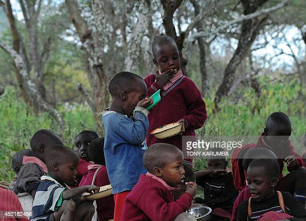 Pupils have lunch in the open before sharing the plates with waiting schoolmates at the Oloserian primary school in Kajiado county some 100...