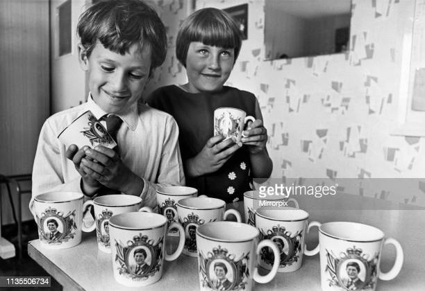 Pupils Ian Graves and Julie Radford admire the mugs presented by Cardiff City Council to children at Bryn Hafod Junior School, Llanrumney, Cardiff,...