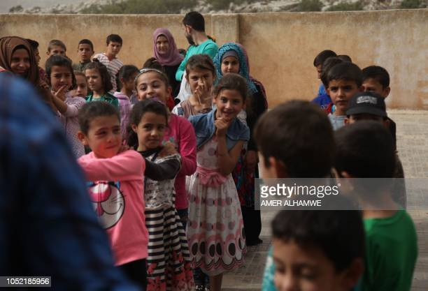Pupils line up in rows in the courtyard of their school in the city of Harim in the rebelheld northern countryside of Syria's Idlib province on...