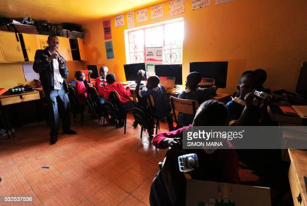 Pupils of Kibera School for Girls learn how to use computers at Nairobi on May 19 2016 Kibera School for Girls offers free tuition uniforms books and...