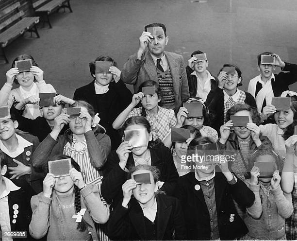 Pupils of South Harringay Primary School in north London and their headmaster view the first eclipse of the sun visible from the British Isles since...