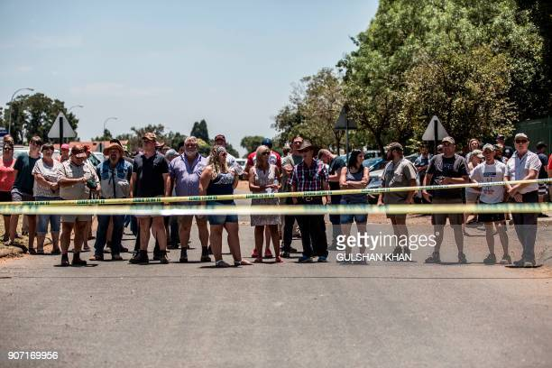 Pupils' parents and other members of the surrounding community stand behind a police line in support of a protest against admission and language...