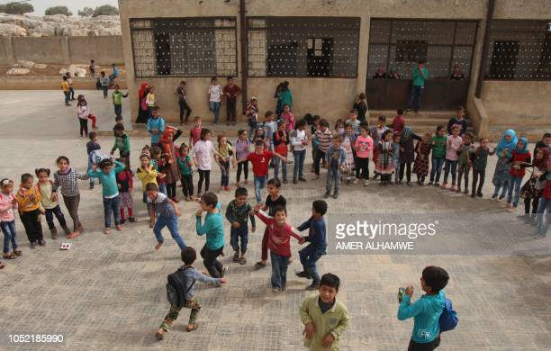 Pupils play in the courtyard of their school in the city of Harim in the rebelheld northern countryside of Syria's Idlib province on October 15 2018...