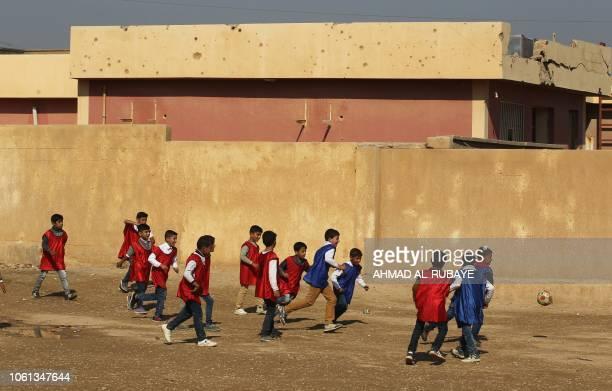 Pupils play in the yard of their school in al-Qaim in the Iraqi Anbar province, opposite Albu Kamal in Syria's Deir Ezzor region, on November 13,...