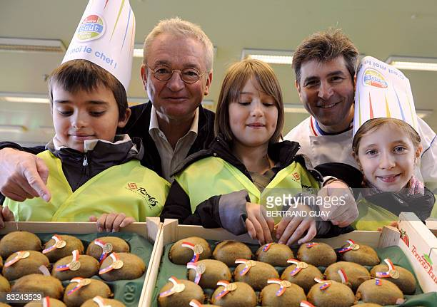 Pupils pose with French journalist JeanLuc Petitrenaud and French Chef Michel Roth on October 13 2008 at Rungis wholesale food market outside Paris...