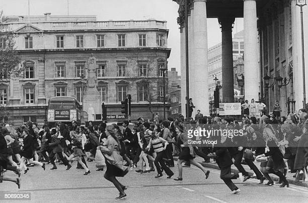 Pupils running across a road during a school strike demonstration Trafalgar Square London 17th May 1972