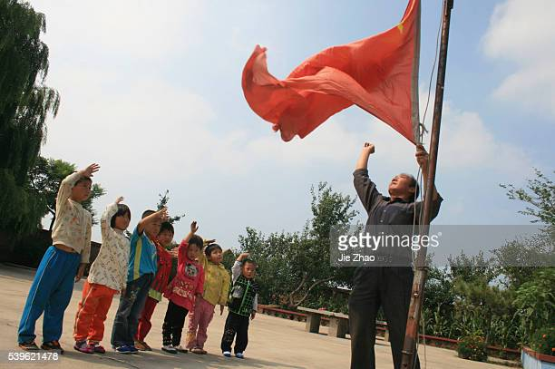 Pupils salute as their teacher raises the Chinese national flag on the first day of their new semester at Gao'er Hope School located on the top of...