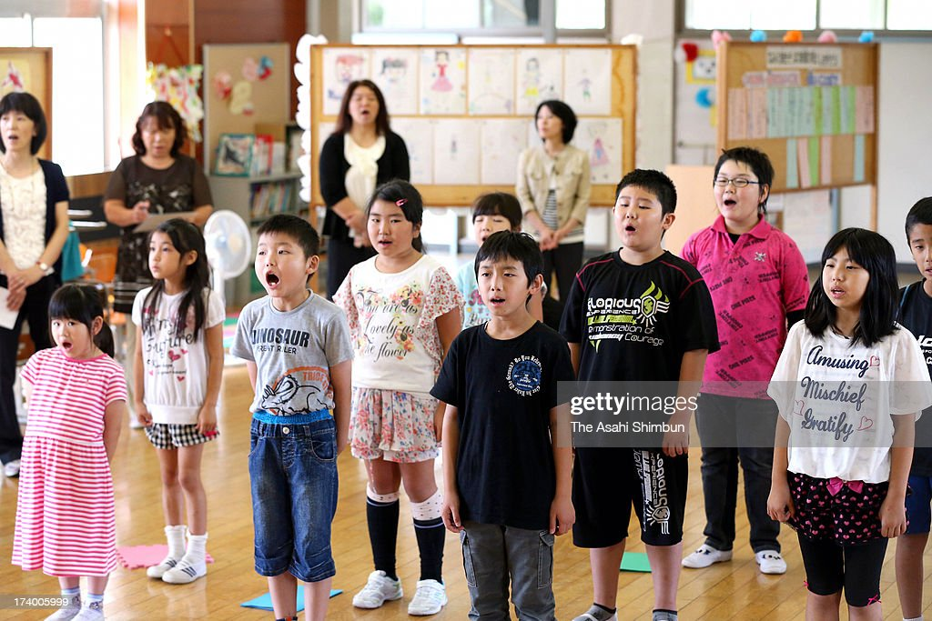 Pupils sing their school songs at the first term ending ceremny as they will enter one-month summer vacation at evacuated Namie Elementary School on July 19, 2013 in Nihonmatsu, Fukushima, Japan. The whole school has been evacuated from Namie town, where the school is only 9 kilometers from crippled Fukushima Daiichi Nuclear Power Plant. The school had no newcomers this year, only 19 pupils are studying, most of them are commuting from temporary housing.