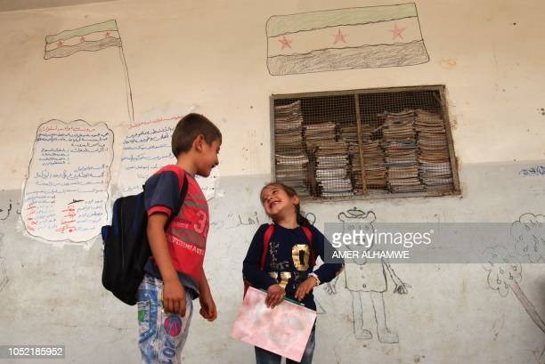 Pupils smile to each other in the courtyard of their school in the city of Harim in the rebelheld northern countryside of Syria's Idlib province on...