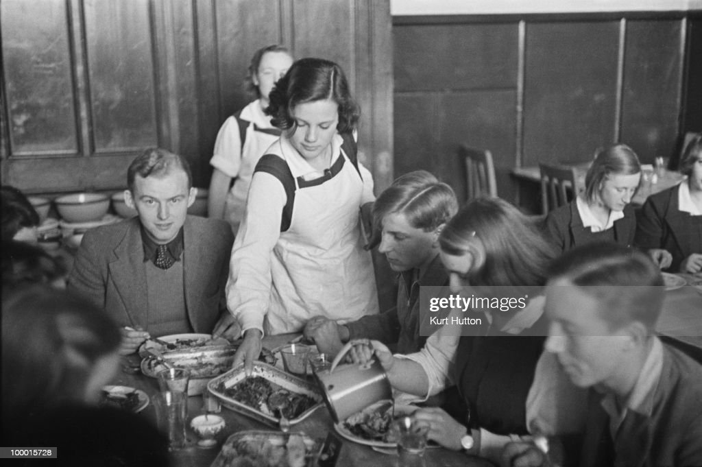 Pupils take turns to wait on one-another in the dining hall at Bedales Boarding School in Steep, Hampshire, January 1941. Original publication: Picture Post - 403 - Bedales Boarding School - pub. 4th January 1941