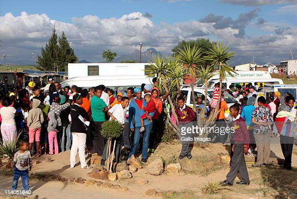 Pupils their parents and community members gather by an ambulance at the Trevor Manual Primary School on May 10 2011 in Fisantekraal near Cape Town...