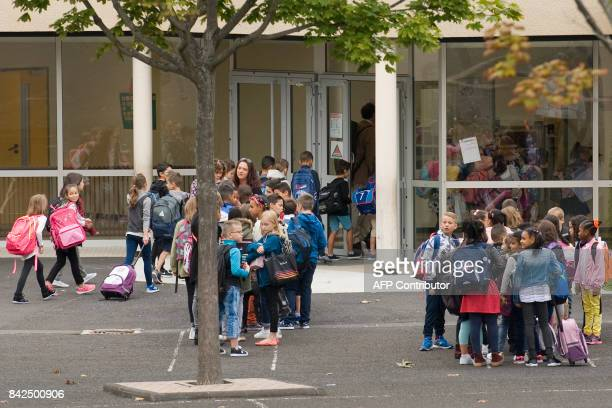Pupils wait to enter in classrooms at the Pierre Mendes France primary school in ClermontFerrand at the start of the new school year on September 4...