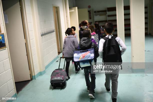 Pupils walk in a corridor at their primary school at the start of the new school year on September 4 in CorbeilEssonnes outside Paris / AFP PHOTO /...
