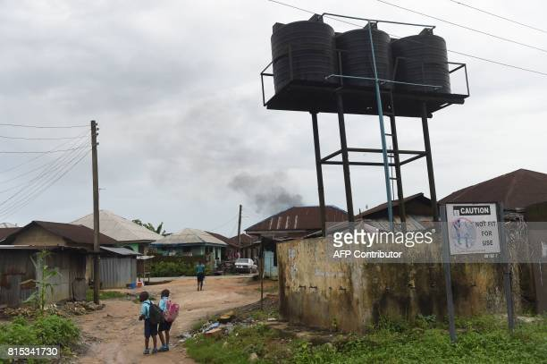 Pupils walk past a contaminated borehole considered unfit for use by the United Nations Environment Programme at Ogale Town NchiaEleme in Rivers...