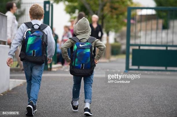 Pupils walk towards the Pierre Mendes France primary school in ClermontFerrand at the start of the new school year on September 4 2017 / AFP PHOTO /...