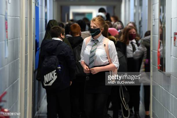 Pupils wear face masks as they walk in a corridor at Springburn Academy school in Glasgow on August 31, 2020 as mandated by new guidance from the...