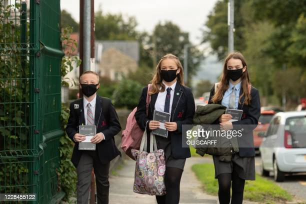 Pupils wearing facemasks as a precaution against the transmission of the novel coronavirus arrive to attend Moor End Academy in Huddersfield,...