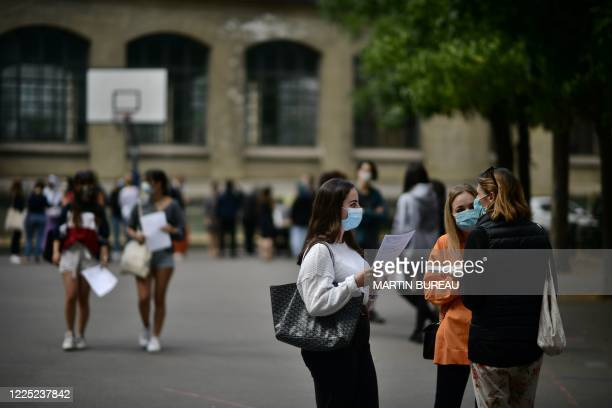 Pupils wearing masks talk in the courtyard as they arrive to learn the outcome of the baccalaureate at the Jean-de-La-Fontaine highschool in the 16th...