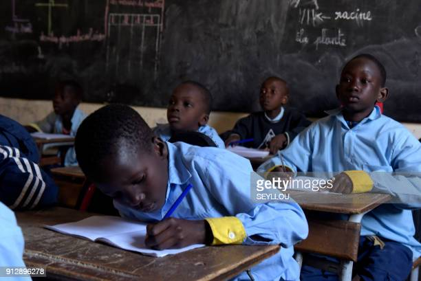 Pupils write on their notebook as they attend class at a primary school in Pikine, on the outskirts of Dakar, on January 30, 2018. Education is a...
