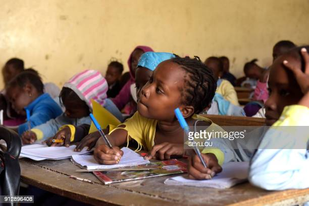 Pupils write on their notebook as they attend class at a primary school in Pikine on the outskirts of Dakar on January 30 2018 Education is a...