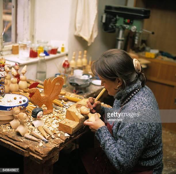 Puppenmacherin schnitzt eine Holzpuppe in ihrer Werkstatt ohne Jahr