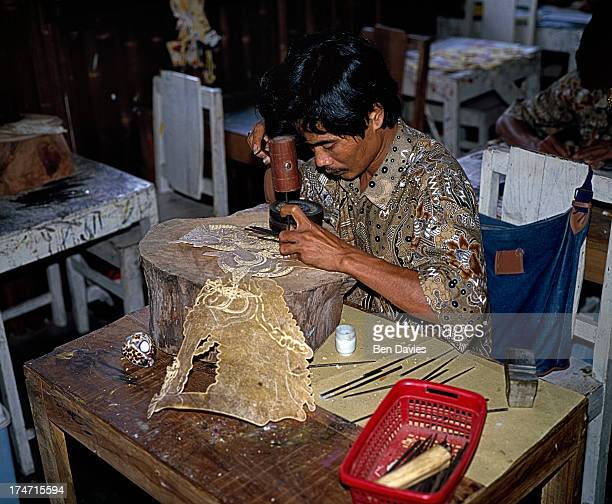 A puppet maker produces 'wayang kulit' or shadow puppets in Yogyakarta the cultural centre of Java Puppet plays have their origins in Hindu epics...