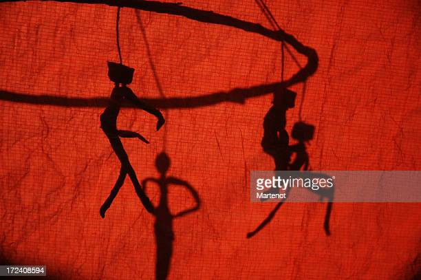 Puppet shadow behind a red curtain