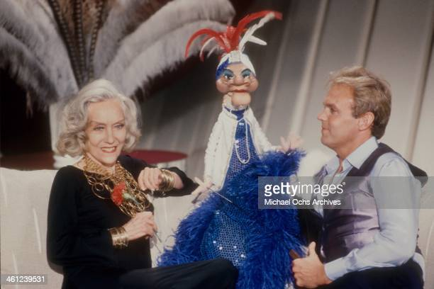 Puppeteer Wayland Flowers and his puppet Madame chat with actress Gloria Swanson on the set of a TV show circa 1980 in Los Angeles California
