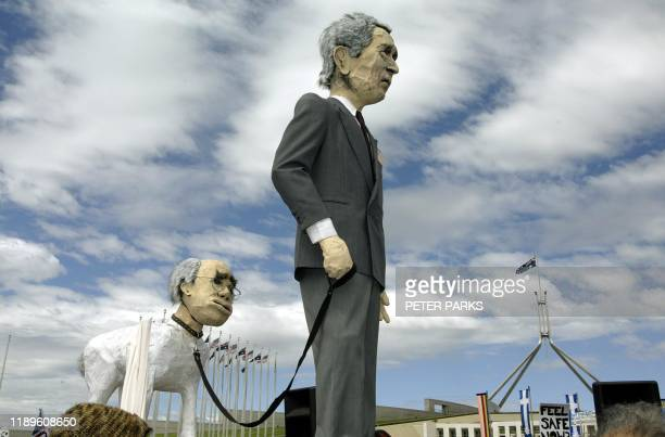 Puppets showing Australian Prime Minister John Howard as US President George W Bush's dog are paraded outside Parliament House in Canberra during a...