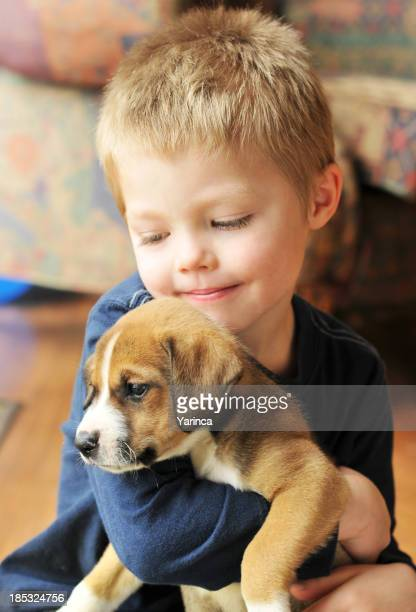 Puppy being held by a toddler boy