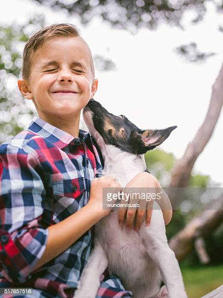 Puppy dog licking mischievous little boy's face in park