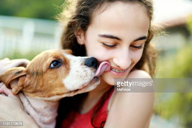 puppy kissing teenage girl - teenagers only stock pictures, royalty-free photos & images