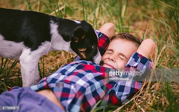 Puppy licking little boy's face who is lying in grass