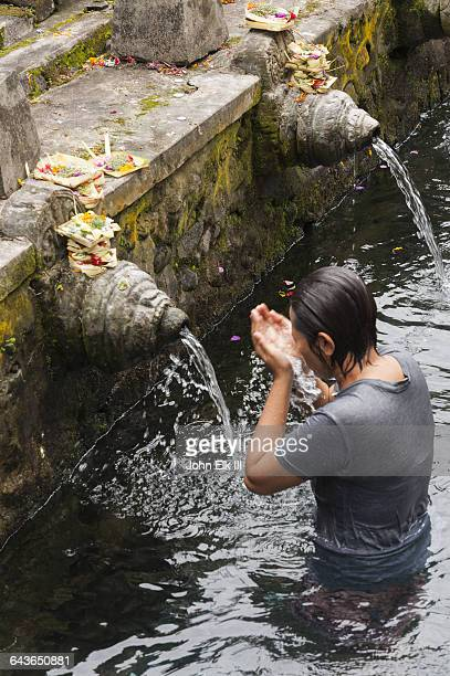 pura tirta empul temple, bathing in sacred spring - pura tirta empul temple stock pictures, royalty-free photos & images