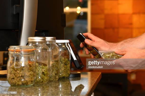 purchasing cannabis with a smart phone - cannabis store stock pictures, royalty-free photos & images