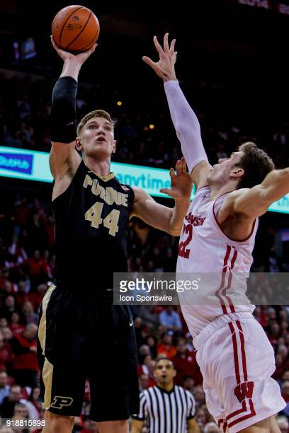 Purdue Boilermakers center Isaac Haas goes up for a shot over Wisconsin Badger forward Ethan Happ during an college basketball game between Purdue...