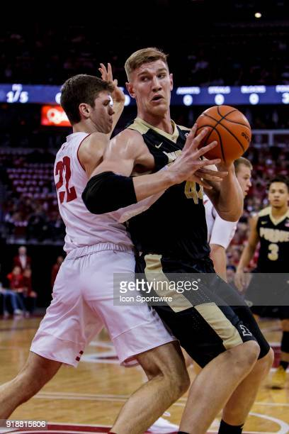 Purdue Boilermakers center Isaac Haas looks to back down Wisconsin Badger forward Ethan Happ to the basket during an college basketball game between...