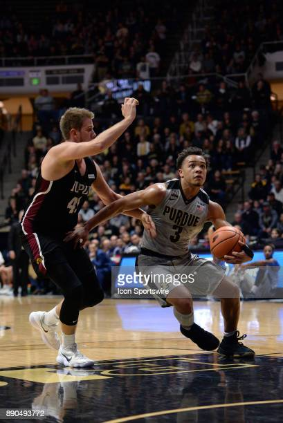 Purdue Boilermakers Guard Carsen Edwards dribbles by IUPUI Jaguars forward Aaron Brennan on a fast break during the college basketball game between...