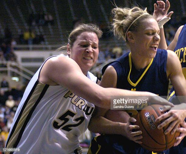Purdue center Emily Heikes and Michigan forward Kelly Helvey scramble for a loose ball. Purdue defeated Michigan 67-66 at Mackey Arena in West...