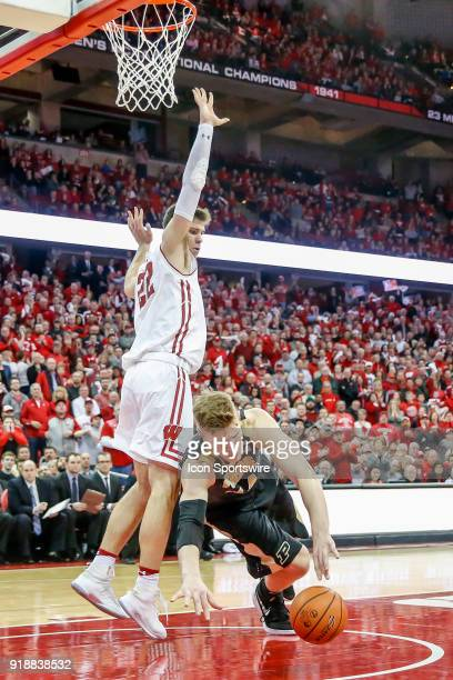 Purdue center Isaac Haas trips and can't hang onto the ball in front of Wisconsin forward Ethan Happ during a college basketball game between the...