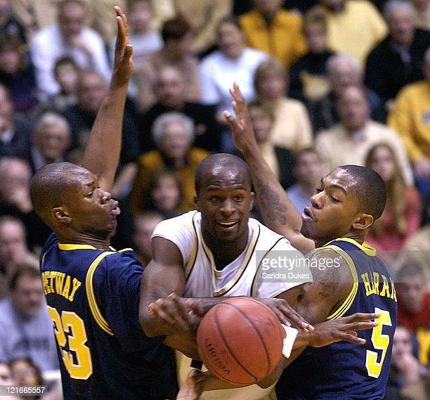 Purdue guard Brandon McKnight slips the ball between Michigan forward Brent Petway and guard Dion Harris Purdue defeated Michigan 8455 at Mackey...