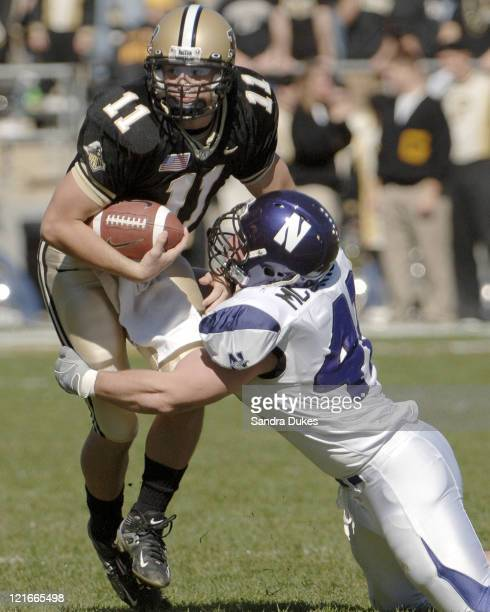 Purdue quarterback Brandon Kirsch looks to run but is wrapped up by Northwestern's Tim McGarigle in the first quarter of Northwestern's 34-29 win...