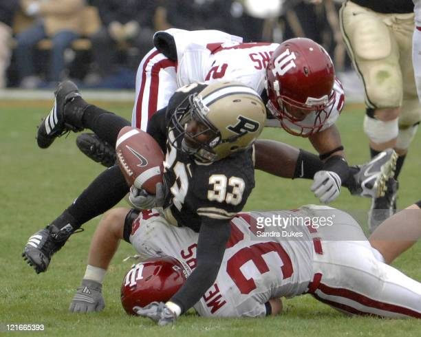 Purdue's RB Jaycen Taylor loses his grip on the ball as he is sandwiched between 2 Indiana players. Purdue defeated Indiana 28-19 in Ross Ade...