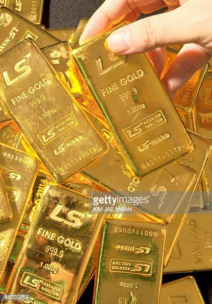 Pure 1000gram gold bars produced by South Korea's LSNikko are stacked in a dealers room in Seoul on January 9 2009 Gold prices have soared on strong...