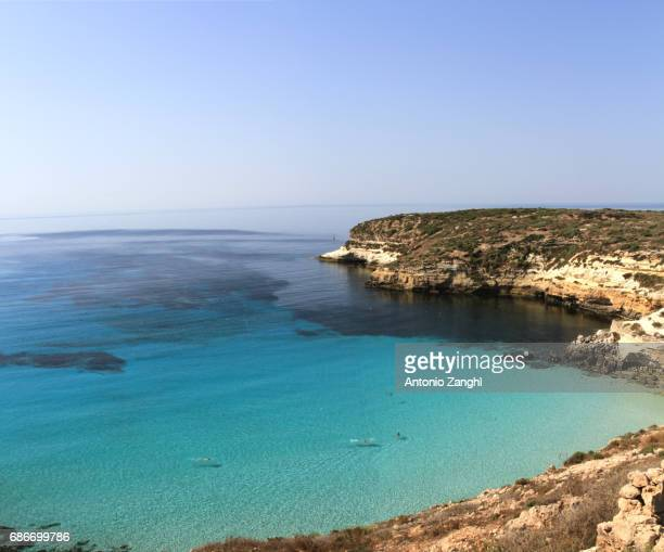 pure crystalline water surface around an island - lampedusa, sicily - rabbit beach stock photos and pictures