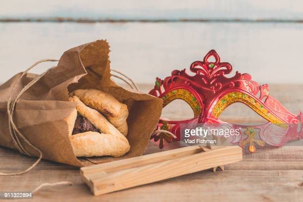 """Purim jewish holiday composition with hamantaschen, purim mask and purim gragger on a vintage wood background with copy space""""r""""n"""