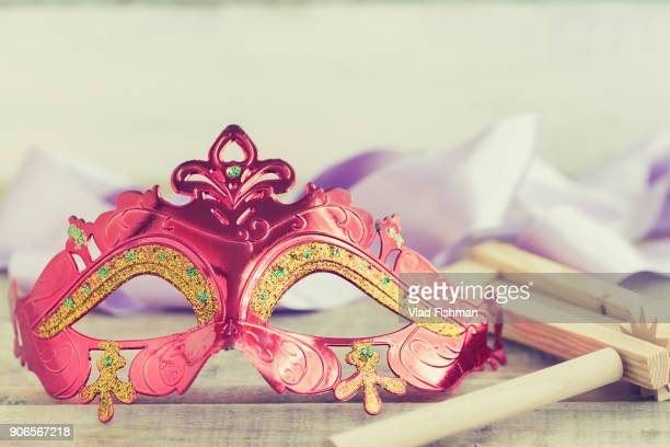 Purim jewish holiday composition with purim mask and purim gragger on a vintage wood background with copys pace