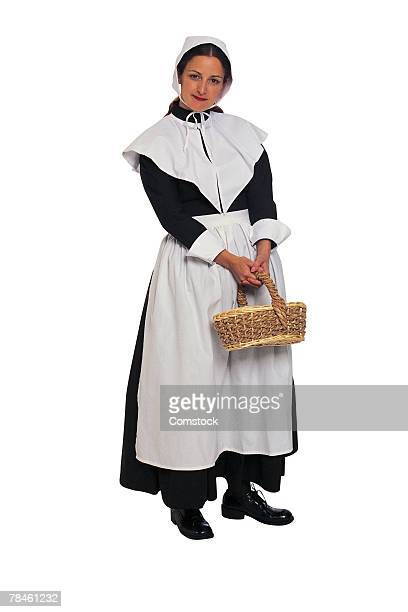 puritan woman settler with basket - puritanism stock photos and pictures