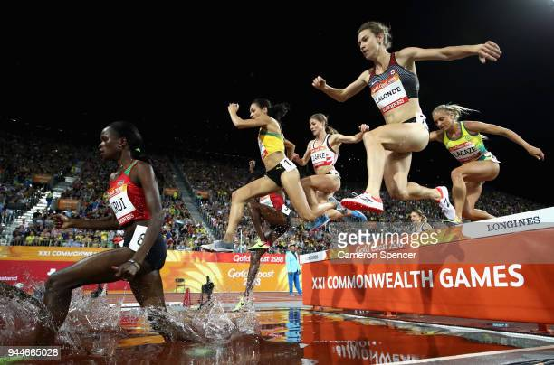 Purity Cherotich Kirui of Kenya Aisha Praught of Jamaica and Genevieve Lalonde of Canada clear the water jump competes in the Women's 3000 metres...