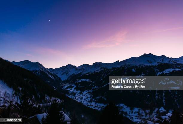 purple and blue sky over snowy mountains during sunset in the swiss alps. - switzerland stock pictures, royalty-free photos & images